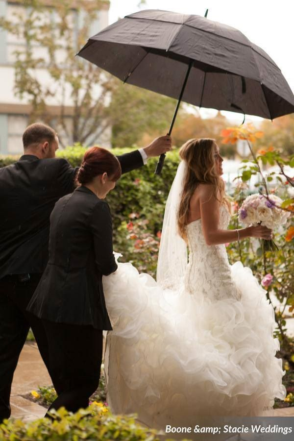 Fairy Godmother Cassandra holding umbrella for bride during wedding procession